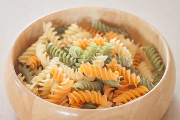 Raw fusilli pasta on wooden bowl Stock photo © punsayaporn