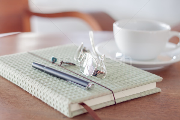 Notebook with pen, eyeglasses and white coffee cup on wooden tab Stock photo © punsayaporn