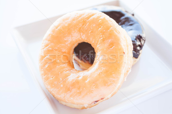 Glazed and chocolate donuts on white plate  Stock photo © punsayaporn