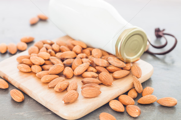 Almond nuts on wooden plate with milk Stock photo © punsayaporn