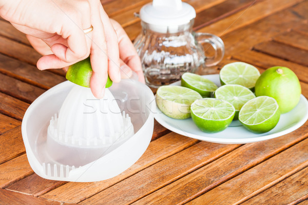Hand squashing fresh lime on wood table Stock photo © punsayaporn