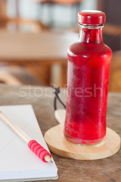 Red syrup in the bottle on wooden plate Stock photo © punsayaporn