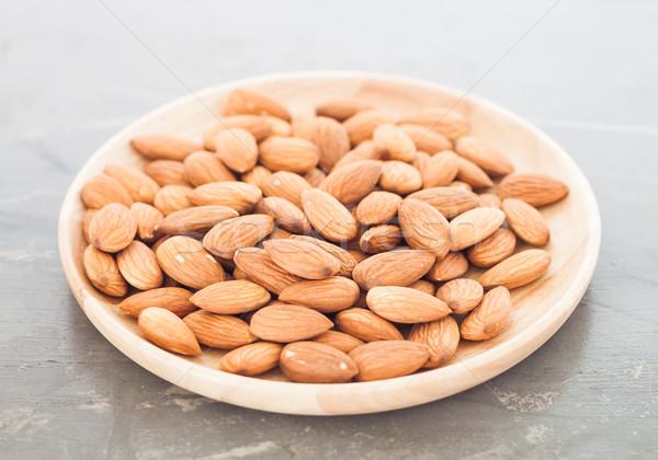 Almond nuts on wooden plate Stock photo © punsayaporn