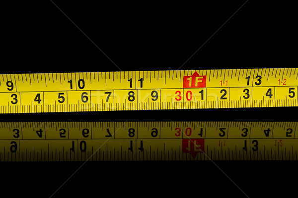 Tape measure in millimetres and inches on black Stock photo © pxhidalgo