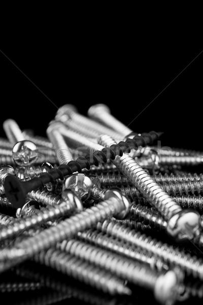 Macro, one black screw in a pile of brass screws Stock photo © pxhidalgo
