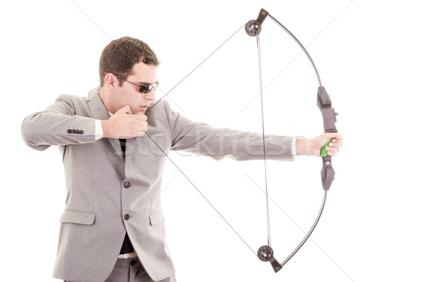 Determined handsome businessman aiming at target with bow Stock photo © pxhidalgo