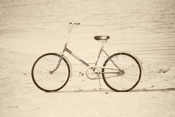 Ancient bicycle on beach - retro sepia Stock photo © pzaxe