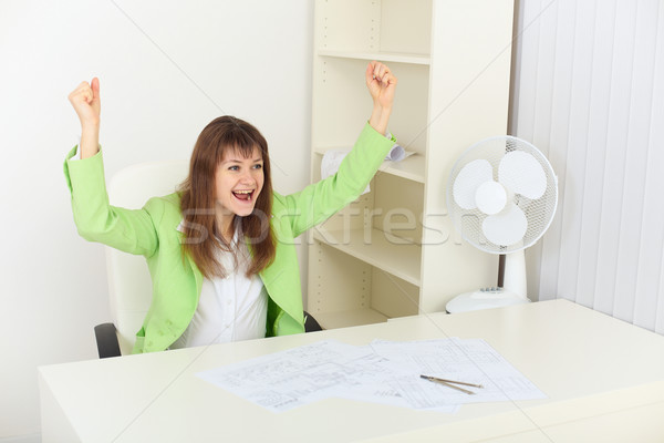 Exulting young woman sits at a table Stock photo © pzaxe