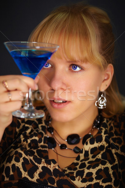Young woman looks at glass with unusual cocktail Stock photo © pzaxe