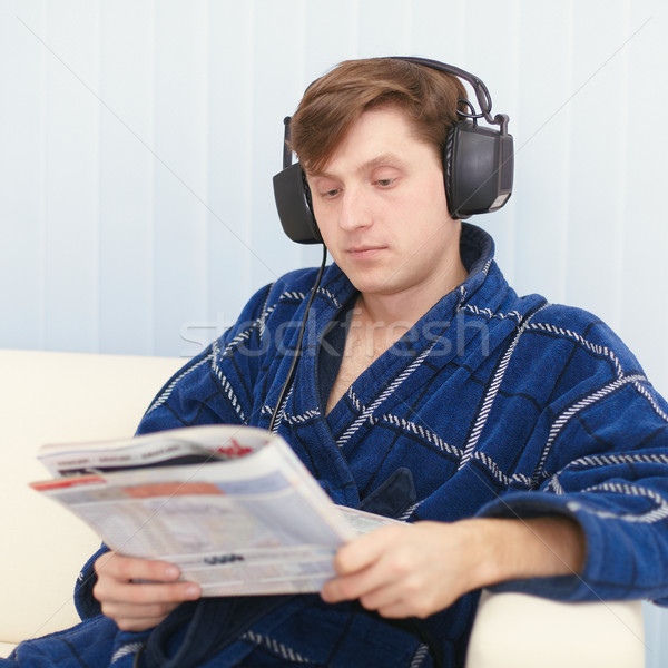 Man in big ear-phones on sofa reads newspaper Stock photo © pzaxe