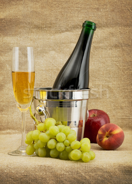 Still life with champagne bottle, goblet and fruits Stock photo © pzaxe
