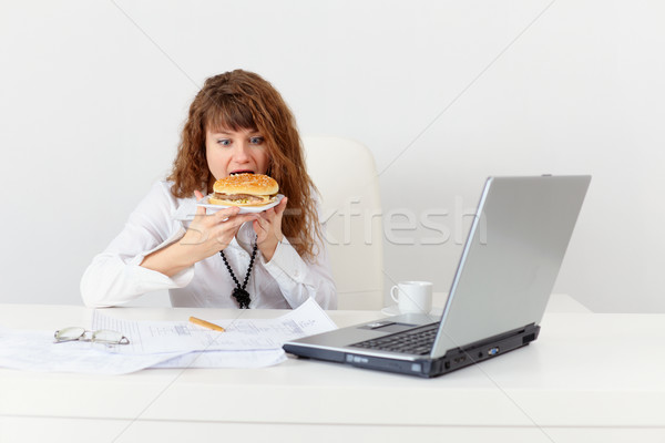 Young girl has hastily dinner sandwich at office Stock photo © pzaxe