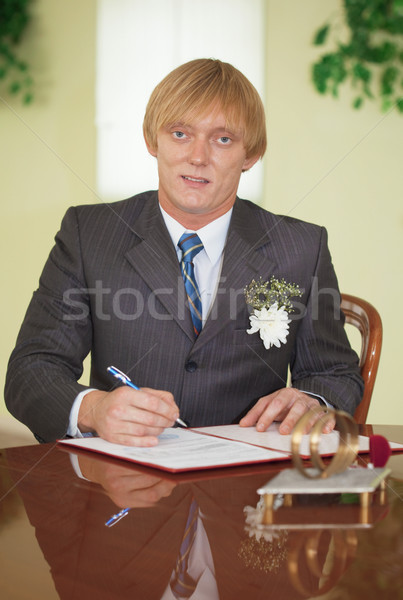 Groom puts signature on registration document Stock photo © pzaxe