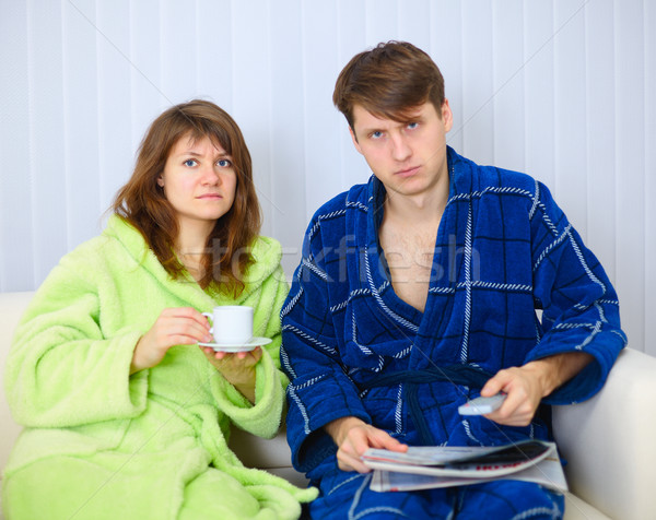 Couple in dressing gowns sitting on couch and watching TV in dis Stock photo © pzaxe