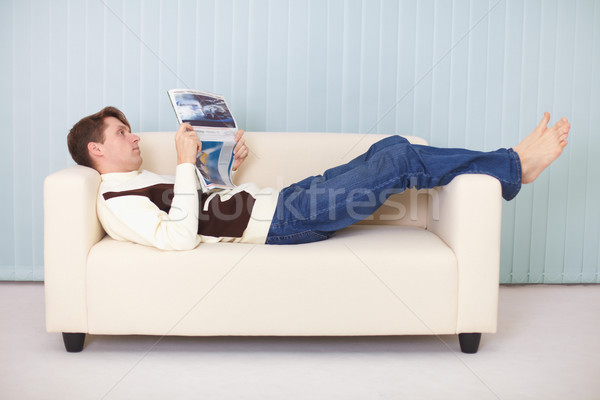 Young man lies comfortably on sofa with a newspaper Stock photo © pzaxe