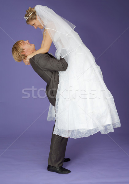 Strong groom holds admired bride on hands Stock photo © pzaxe