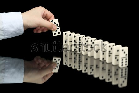 Hand pushing dominoes counters on black Stock photo © pzaxe