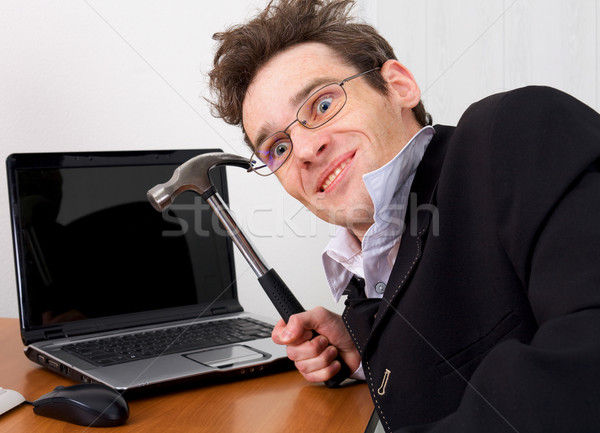 Businessman in spectacles gone mad with a hammer Stock photo © pzaxe