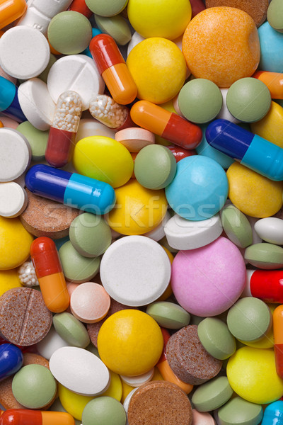 Pile of colorful medications tablets - medical background Stock photo © pzaxe