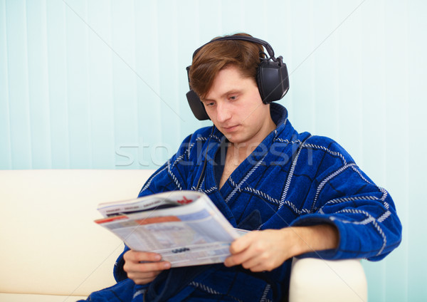Person in big ear-phones on sofa reads newspaper Stock photo © pzaxe