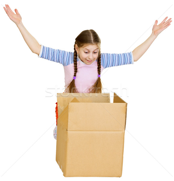 Stock photo: Little girl joyfully looks in a box