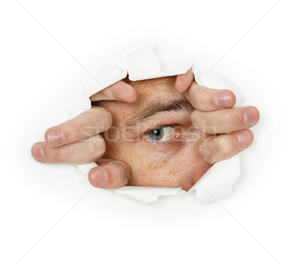 Man looks through a hole in paper Stock photo © pzaxe