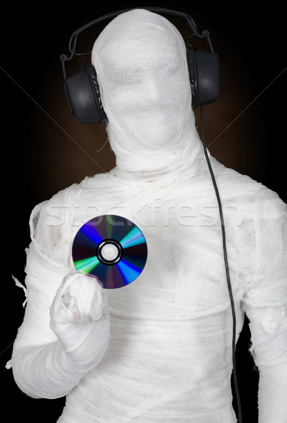 Stock photo: Man in bandage with ear-phones and disc