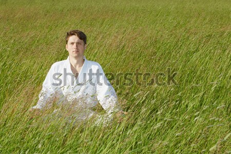 Young man sits in a grass Stock photo © pzaxe