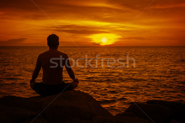Man meditating at sunset. Tropical beach of Thailand Stock photo © pzaxe