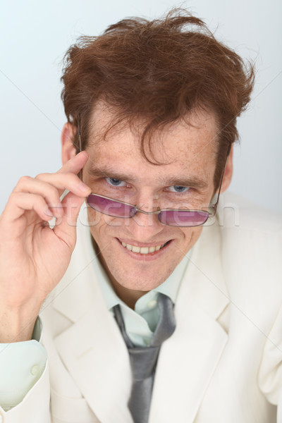 Cheerful tousled guy looks over eyeglasses Stock photo © pzaxe