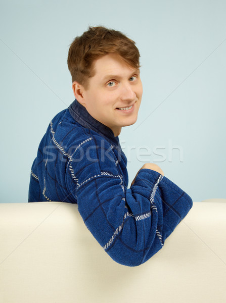 Happy smiling man sitting on couch in dressing gown Stock photo © pzaxe