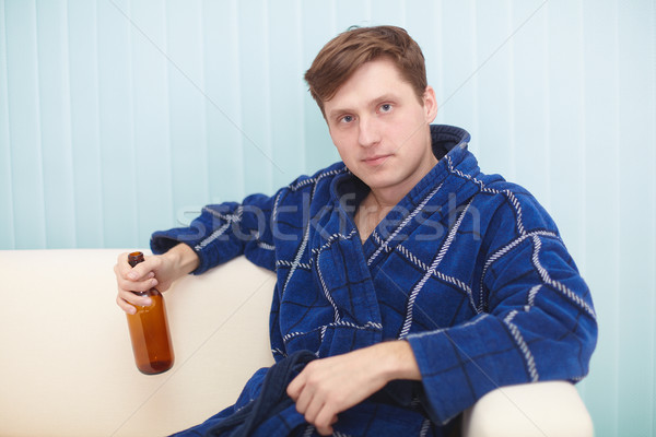 Young man in dressing gown sits on a couch with bottle Stock photo © pzaxe