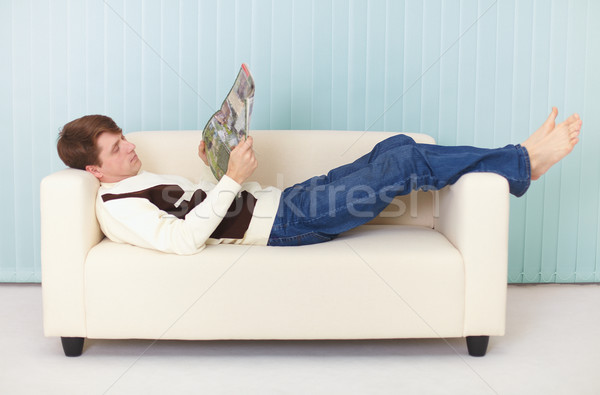 Young woman lies comfortably on sofa with a magazine Stock photo © pzaxe