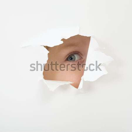Eye looking through hole in sheet of paper Stock photo © pzaxe