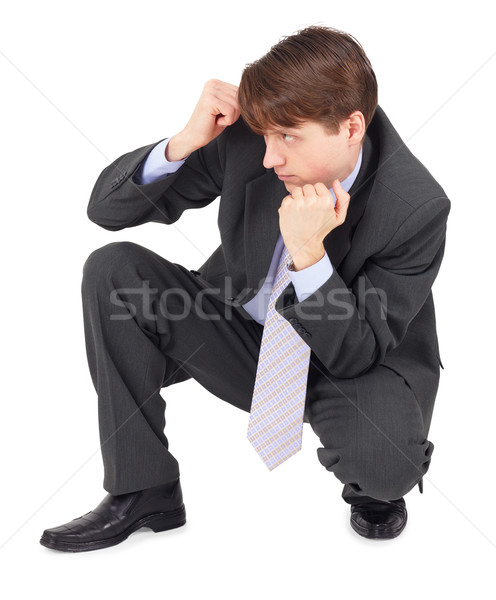 Young man sits in a defensive pose on white Stock photo © pzaxe
