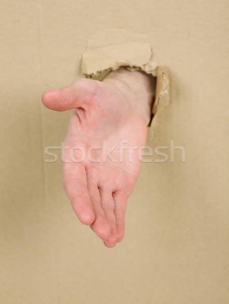 Male hand throug in cardboard Stock photo © pzaxe