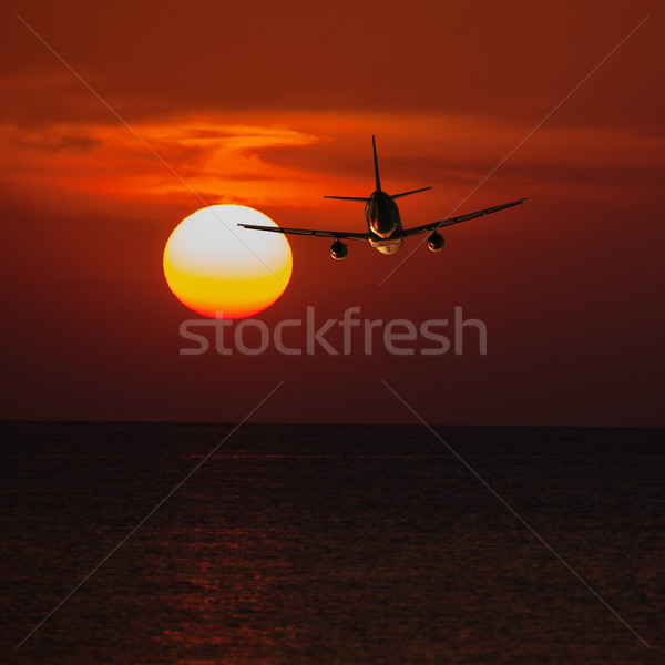 Passenger plane flying at a low altitude at sunset and the sun b Stock photo © pzaxe