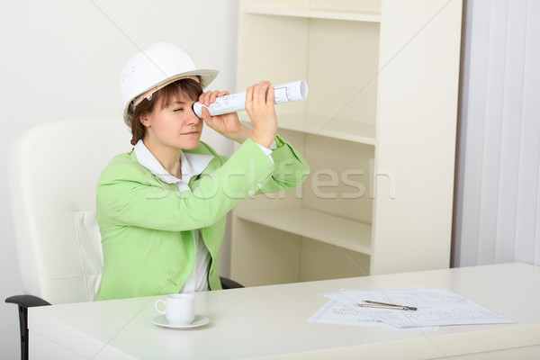 Young woman in helmet sits at table with draft in hands Stock photo © pzaxe