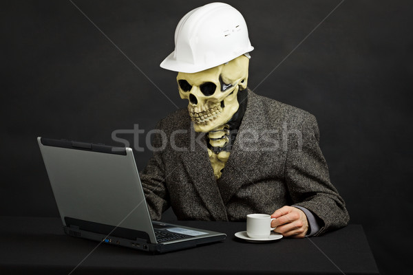 Stock photo: Comical man in helmet and skeleton mask with computer