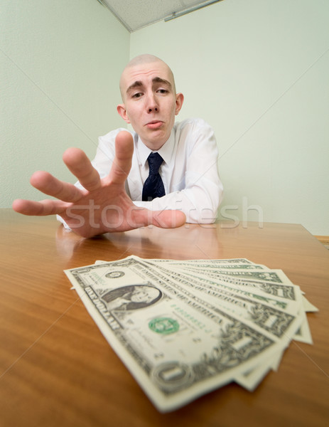 Man reaches for a batch of money Stock photo © pzaxe