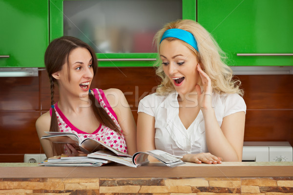 Funny girlfriends browsing magazines on kitchen Stock photo © pzaxe