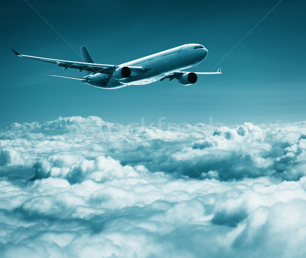 Passenger plane flies over cumulus clouds Stock photo © pzaxe