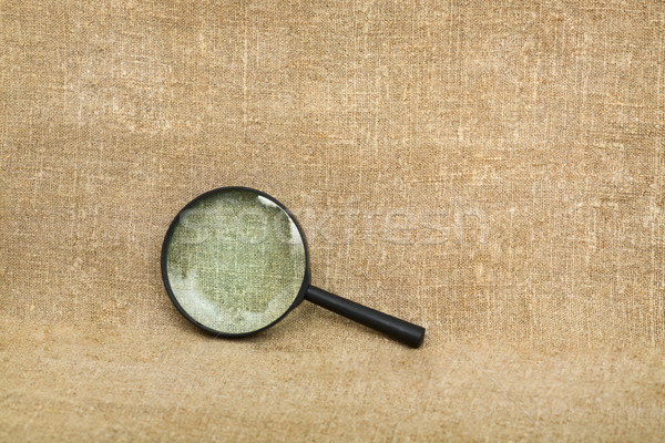 Old magnifier on brown canvas background Stock photo © pzaxe