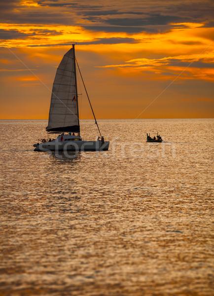 Catamarán velero tropicales mar puesta de sol cielo Foto stock © pzaxe