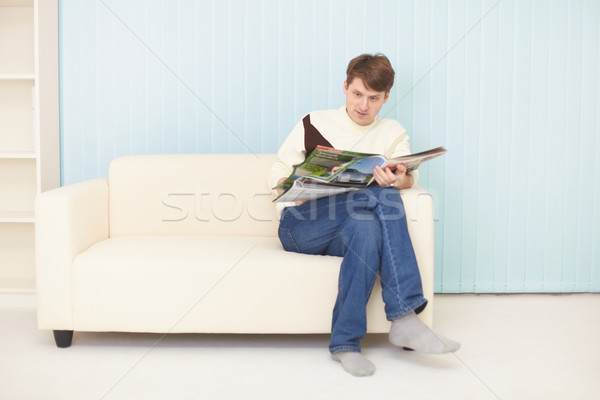 Young man sits on sofa with journal Stock photo © pzaxe