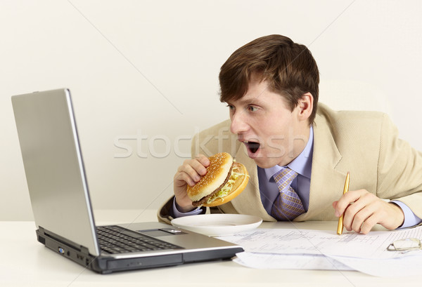 Stock photo: Young businessman is going to eat sandwich