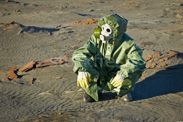 Scientist in protective suit and gas mask sitting on slag Stock photo © pzaxe