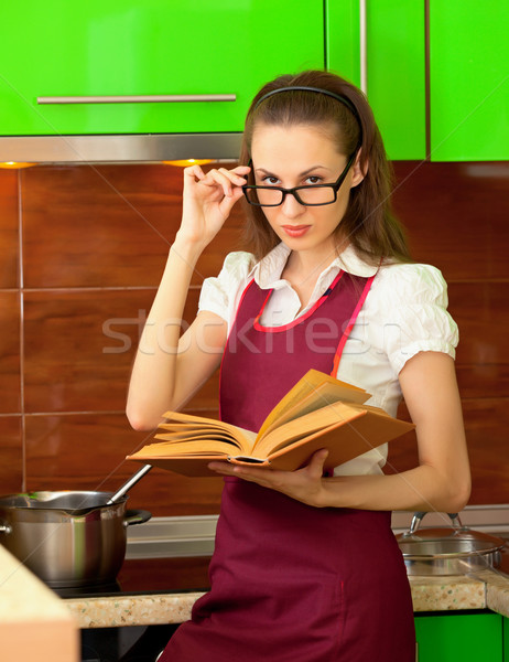 Girl reading a cookbook on kitchen Stock photo © pzaxe