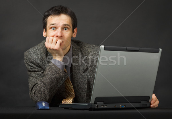 Surprised person with computer. Sits and thinks. Stock photo © pzaxe