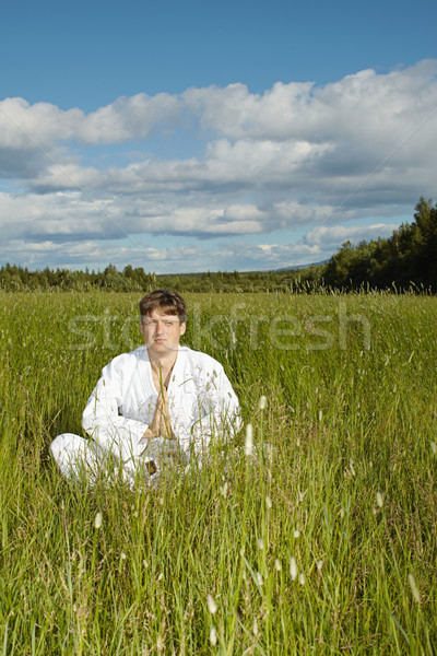 Young man meditates in a field Stock photo © pzaxe